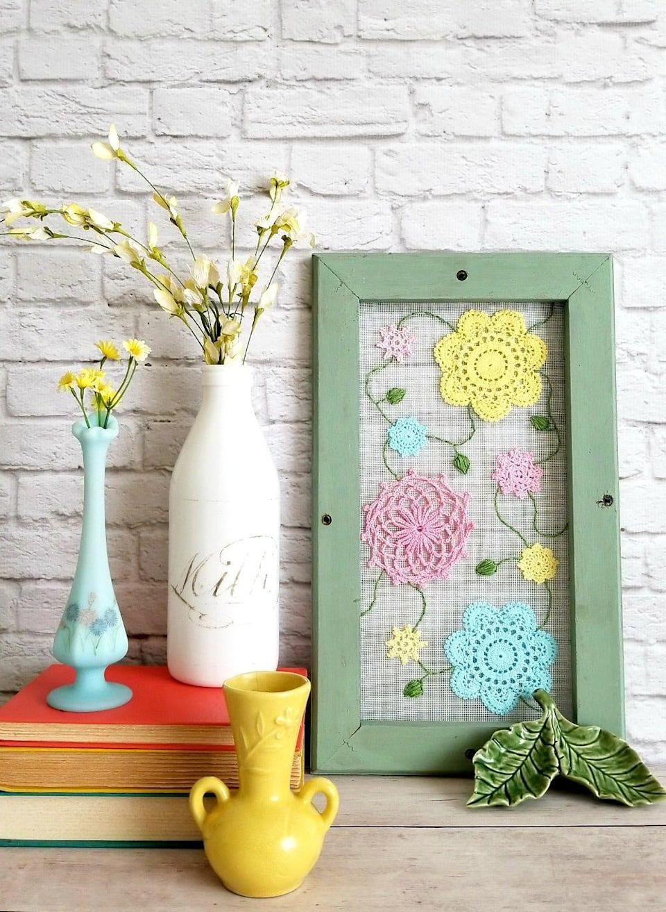"""<p>Add screen mesh to a cute frame from the dollar store to show off pastel paper doilies-turned-flowers.</p><p><em><a href=""""https://www.sadieseasongoods.com/cottage-style-spring-decor/"""" rel=""""nofollow noopener"""" target=""""_blank"""" data-ylk=""""slk:Get the tutorial at Sadies Seasonsgoods »"""" class=""""link rapid-noclick-resp"""">Get the tutorial at Sadies Seasonsgoods »</a></em></p>"""