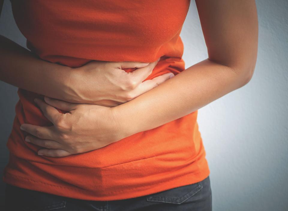 Woman holding stomach cramps digestive problems