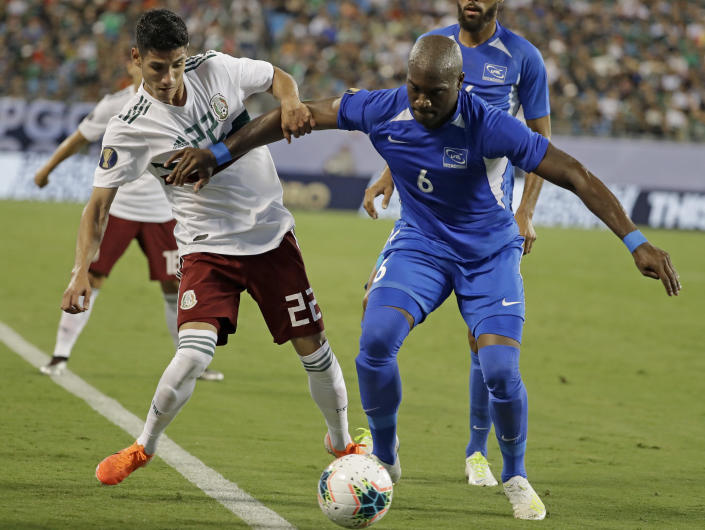 Mexico's Jorge Sanchez (22) battles Martinique's Jean-Sylvain Babin (6) during the first half of a CONCACAF Golf Cup soccer match in Charlotte, N.C., Sunday, June 23, 2019. (AP Photo/Chuck Burton)