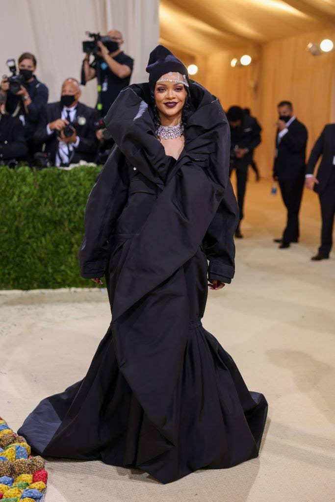 Rihanna wore a dark colored gown with a high collar and a beanie