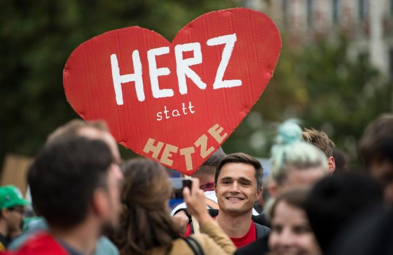 "A demonstrators brandishes a sign reading ""Heart instead of hate"" at the rally, which drew 8,000 supporters and opponents of Germany's immigration policy"