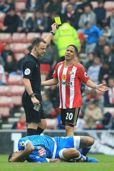 Sunderland's Steven Pienaar (R) gets a yellow card from referee Stuart Attwell (L) during their English Premier League football match against Bournemouth on April 29, 2017