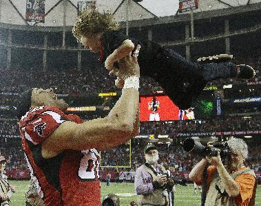 Atlanta Falcons tight end Tony Gonzalez (88) holds his son river Gonzales, 3, during a celebration of Gonzalez career before the second half of an NFL football game against the Carolina Panthers, Sunday, Dec. 29, 2013, in Atlanta. (AP Photo/John Bazemore)