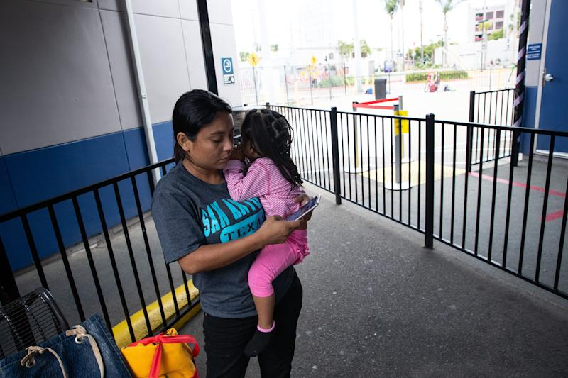 SAN DIEGO – Delmy López, 31, a migrant from Honduras, messages her brother in-law as she holds her 2-year-old daughter, Perla, at a Greyhound station at the end of their two day-trip from San Antonio, Texas, to San Diego on June 29, 2019.
