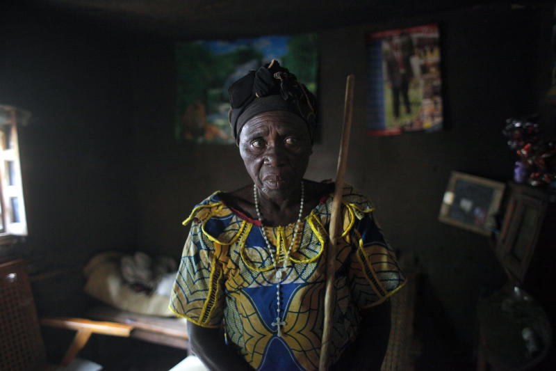 Charlotte Ntibatekereza, whose son, daughter-in-law and grandson were shot in the fighting in Kiwanja, on July 25 2012, stands in her house Sunday, Aug. 5, 2012, in Kiwanja, Congo. Her relatives were sleeping on the floor when a heavy-caliber bullet smashed through three walls of their home. Her son and grandson died instantly. (AP Photo/Jerome Delay)
