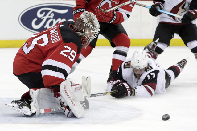 New Jersey Devils goaltender MacKenzie Blackwood (29) protects the net as Arizona Coyotes center Alex Galchenyuk (17) falls to the ice while attacking during the first period of an NHL hockey game, Saturday, March 23, 2019, in Newark, N.J. (AP Photo/Julio Cortez)