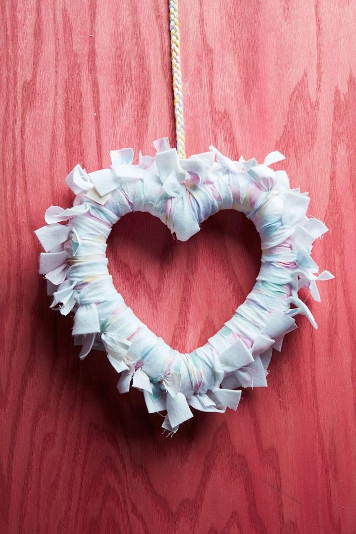 """<p>Wrap strips of soft flannel around a heart-shaped foam wreath form to create a soft statement piece that says """"I love you!""""</p><p><a class=""""link rapid-noclick-resp"""" href=""""https://www.amazon.com/Decorate-Garland-Valentines-Decoration-Rely2016/dp/B0799MLQTQ/ref=sr_1_9?tag=syn-yahoo-20&ascsubtag=%5Bartid%7C10050.g.1584%5Bsrc%7Cyahoo-us"""" rel=""""nofollow noopener"""" target=""""_blank"""" data-ylk=""""slk:SHOP WREATH FORM"""">SHOP WREATH FORM</a></p>"""