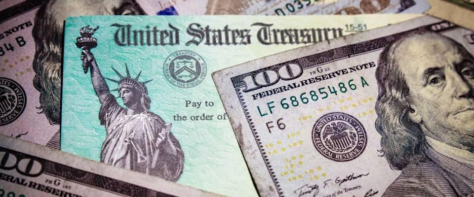 WASHINGTON DC - APRIL 2, 2020: United States Treasury check with US currency. Represents COVID stimulus check.