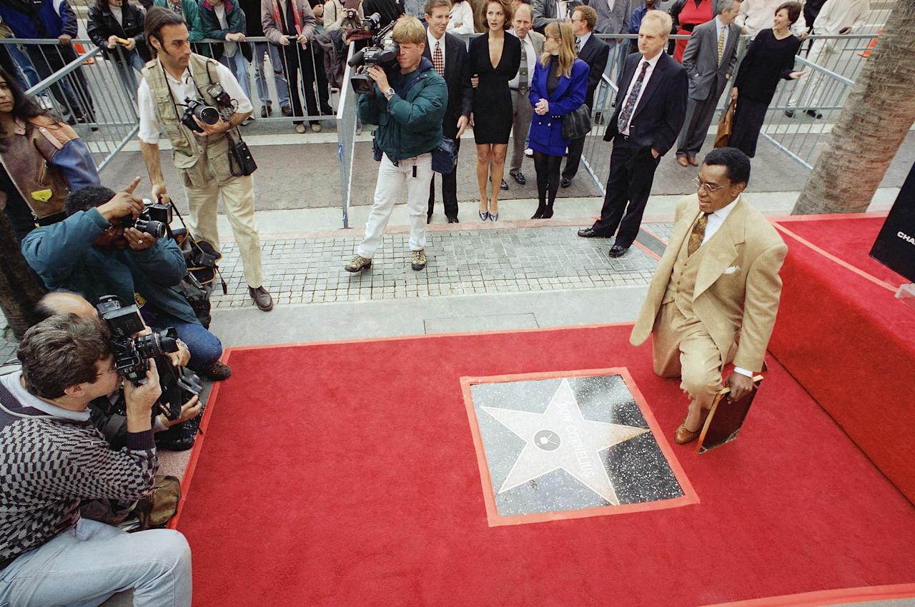 Television producer Don Cornelius kneels in front of photographers near his own star on the Hollywood Walk of Fame during an unveiling ceremony in Los Angeles, Thursday, Feb. 27, 1997. Cornelius is the executive producer and creator of ?Soul Train,? which is now its 27th season. (AP Photo/John Hayes)