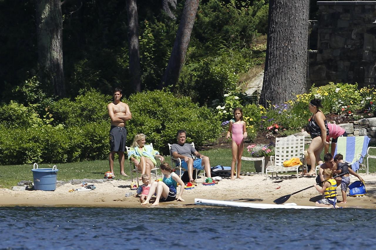 Republican presidential candidate, former Massachusetts Gov. Mitt Romney, his wife Ann, and family members sit on the beach in front of their vacation home on Lake Winnipesaukee in Wolfeboro, N.H., Monday, July 2, 2012. (AP Photo/Charles Dharapak)