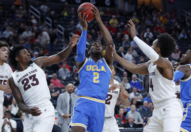 UCLA's Cody Riley, center, grabs a rebound over Arizona State's Romello White, left, and Kimani Lawrence, right, during the first half of an NCAA college basketball game in the quarterfinals of the Pac-12 men's tournament Thursday, March 14, 2019, in Las Vegas. (AP Photo/John Locher)