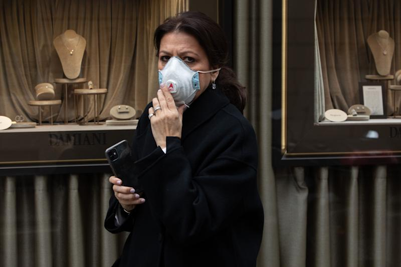 MILAN, ITALY - FEBRUARY 25: A woman, wearing a respiratory mask, walks past a jewelry window in Via Montenapoleone, Milan's fashion district, on February 25, 2020 in Milan, Italy. Italy is the last country to be hit hard by the virus with 7 dead and more than 283 infected as of today. The spread marks Europe's biggest outbreak, prompting the Italian Government to issue draconian safety measures. (Photo by Emanuele Cremaschi/Getty Images) (Photo: Emanuele Cremaschi via Getty Images)