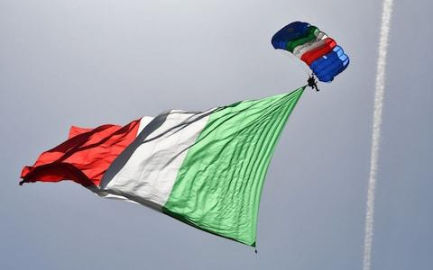 An Italian Army parachutist flies the Italian national flag during a ceremony marking the anniversary of the Italian Republic (Republic Day) - Credit: ALBERTO PIZZOLI/AFP