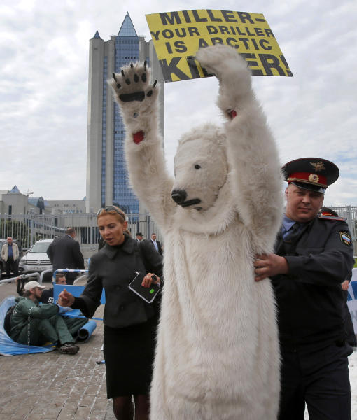 A police officer detains s Greenpeace activist dressed as a polar bear outside Gazprom's headquarters in Moscow, Russia, Wednesday, Sept. 5, 2012. Russian and international environmentalists are protesting against Gazprom's plans to pioneer oil drilling in the Arctic. (AP Photo/Misha Japaridze)