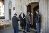 The Imam of the Grand Mosque Sami Fetahu, second left, disinfects the hands of a limited number of Muslim faithfuls attending the Friday prayer in coordination with latest government Covid-19 measures, in Kosovo's capital Pristina on Friday, April 9, 2021. The coronavirus pandemic is imposing a different way of fasting and respect of other religious rights for the Muslim faithful in Kosovo. (AP Photo/ Visar Kryeziu)