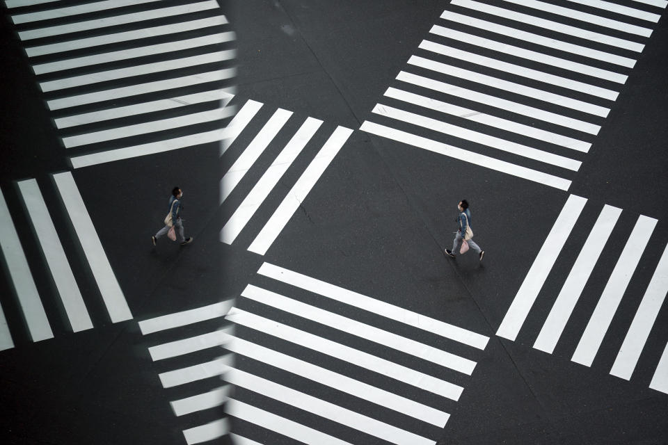A man wearing a protective mask to help curb the spread of the coronavirus runs across a pedestrian crossing Wednesday, Nov. 25, 2020, in Tokyo. The Japanese capital confirmed more than 400 new coronavirus cases on Wednesday. (AP Photo/Eugene Hoshiko)