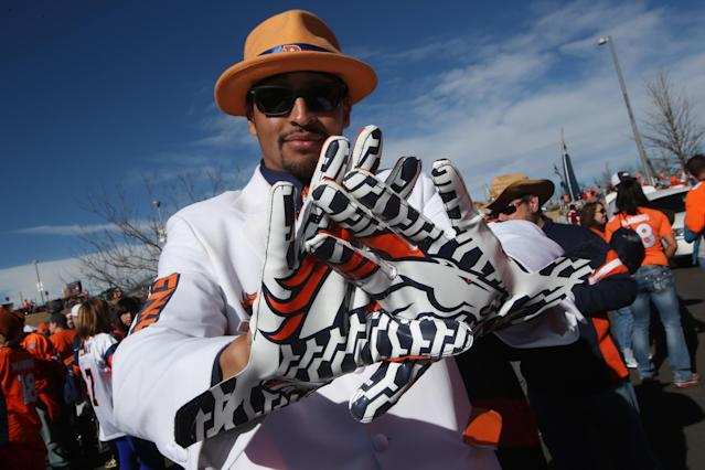 Denver Broncos fan Justin Grimmett, of Denver, shows off his gloves printed with the team logo as he waits to watch the Broncos face the New England Patriots in the AFC Championship NFL football game in Denver, Sunday, Jan. 19, 2014. (AP Photo/David Zalubowski)