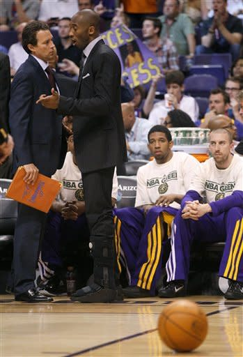 Los Angeles Lakers' Kobe Bryant, right, talks with assistant coach Quinn Snyder during the second half of an NBA basketball game against the Phoneix Suns, Saturday, April 7, 2012, in Phoenix. (AP Photo/Matt York)