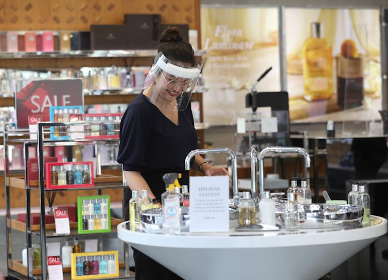 A shop assistant wearing a protective face visor in a fragrance store in Oxford Street, as London prepare to reopen to the public when the lifting of further lockdown restrictions in England comes into effect on Saturday. Picture date: Friday July 3, 2020.