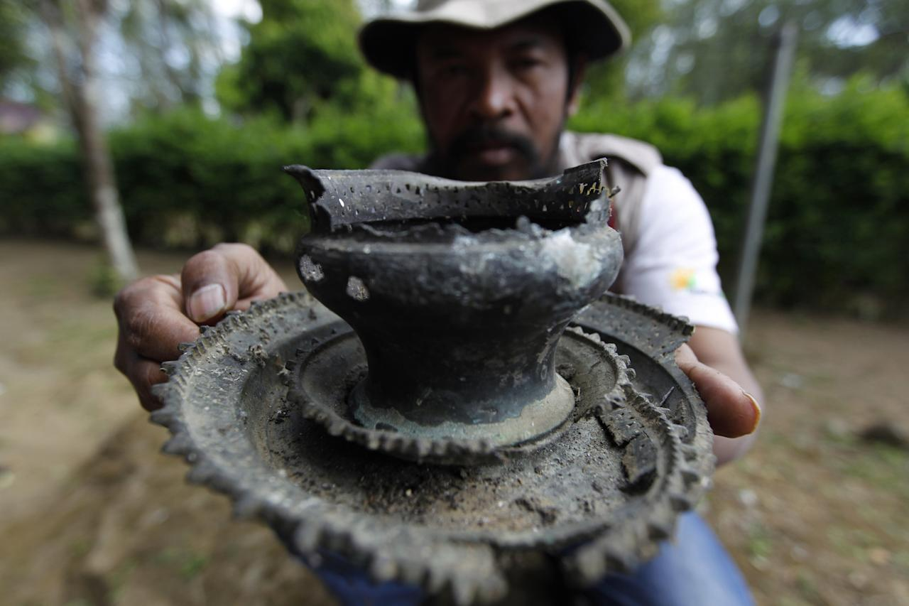 In this photo taken June 23, 2011, an archaeologist working along the flanks of Mount Tambora shows unearthed remnants of villages that were buried beneath up to 3 meters of ash. This artifact, used to grind spices, was found beneath an area that has since been turned into a coffee plantation. (AP Photo/KOMPAS Images, Fikria Hidayat) EDITORIAL USE ONLY