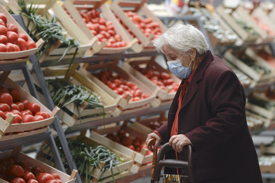 An elderly lady wearing a mask for protection against COVID-19 infection looks at vegetables after the opening of a market selling Romanian food products discounted by 25 percent for pensioners and 15 percent for students living or studying in the district surrounding,in Bucharest, Romania, Saturday, Sept. 19, 2020. Several community welfare investments were inaugurated in the recent weeks as Romania approaches the end of local elections electoral campaign, although the events were not officially related to the upcoming ballot on Sept. 27. (AP Photo/Andreea Alexandru)