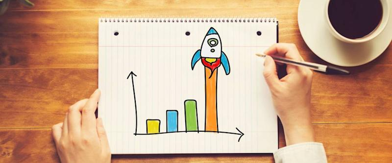 Rocket Graph with a person holding a pen on a wooden desk