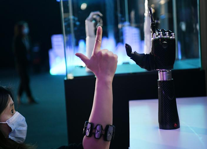BEIJING, Nov. 25, 2020 -- An employee demonstrates a wearable AI-powered bionic hand at the JD Global Technology Discovery Conference in Beijing, capital of China, Nov. 25, 2020. The conference, sponsored by JD.com, a leading e-commerce platform in China, kicked off here on Wednesday under the theme of