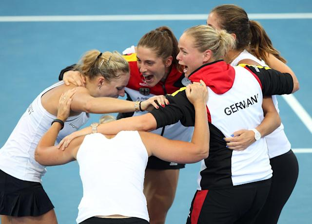 German team members Andrea Petkovic, Julia Georges, Anna-Lena Groenfeld, team captain Barbara Rittner and Angelique Kerber celebrate after defeating Australia 3-0 during their Fed Cup semifinals in Brisbane, Australia, Sunday, April 20, 2014. (AP Photo/Tertius Pickard)