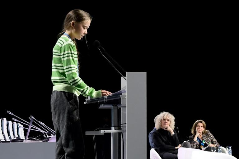 Swedish climate activist Greta Thunberg gives a speech during the COP25 UN Climate Change Conference in Madrid with Greenpeace International executive director Jennifer Morgan, and Spanish environment minister Teresa Ribera in the background (AFP Photo/CRISTINA QUICLER)