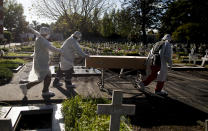 Cemetery workers push the coffin of a COVID-19 victim at a cemetery in Buenos Aires, Argentina, Saturday, May 8, 2021. Argentina has so far reported more than 67,300 confirmed deaths and more than 3.1 million people sickened by the disease. (AP Photo/Natacha Pisarenko)