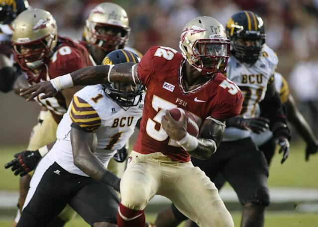 Florida State running back James Wilder Jr. (32) gets past Bethune-Cookman linebacker Jarkevis Fields (1) for a 20-yard run in the second quarter of an NCAA college football game on Saturday, Sept. 21, 2013, in Tallahassee, Fla. (AP Photo/Phil Sears)