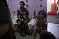 Thayane, who used to make a living as a manicurist, breastfeeds her one-year-old daughter Mirella in their room of an occupied building where she lives with her three daughters, in Rio de Janeiro, Brazil, Thursday, March 11, 2021. Before the coronavirus pandemic hit Thayane had steady work as a manicurist, riding her bike to clients' homes or receiving walk-ins at the squat. (AP Photo/Silvia Izquierdo)