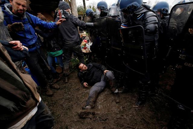 <p>A protester lies in the mud as French gendarmes form a barrier during an evacuation operation in the zoned ZAD (Deferred Development Zone) in Notre-Dame-des-Landes, near Nantes, France, April 9, 2018. (Photo: Stephane Mahe/Reuters) </p>