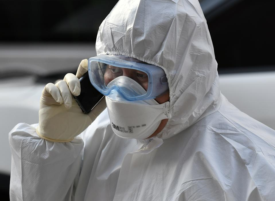 A South Korean medical worker wearing protective gear speaks over a phone as he visits a residence of people with suspected symptoms of the COVID-19 coronavirus to take samples, near the Daegu branch of the Shincheonji Church of Jesus in Daegu on February 27, 2020. - South Korea now has 1,766 cases, the highest number in the world outside China, where the disease first emerged in December and has since spread to dozens of countries. (Photo by Jung Yeon-je / AFP) (Photo by JUNG YEON-JE/AFP via Getty Images)