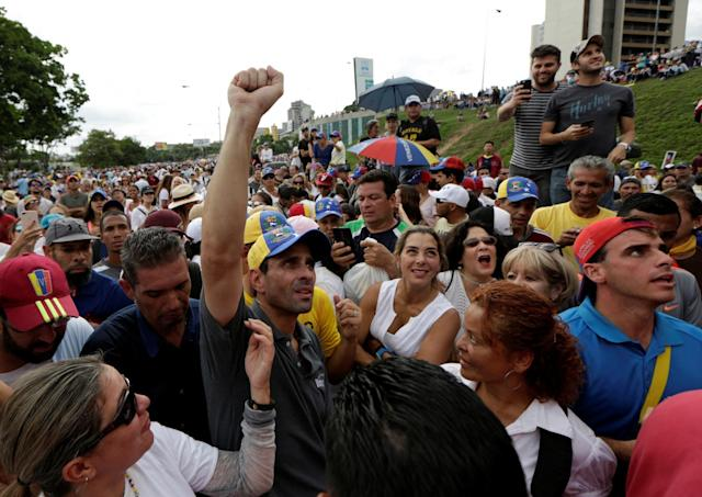 <p>Venezuela's opposition leader and Governor of Miranda state Henrique Capriles (L) poses for a picture with supporters during a blockade in an avenue while rallying against President Nicolas Maduro in Caracas, Venezuela, May 15, 2017. (Marco Bello/Reuters) </p>