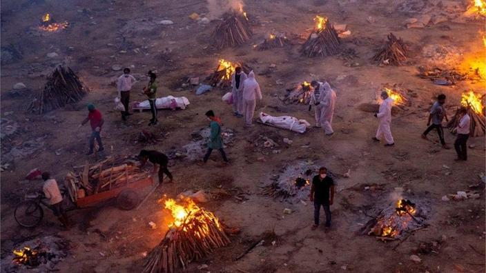 People walk past funeral pyres in New Delhi, India, April 2021