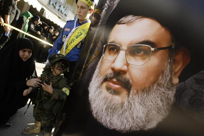 A boy dressed in military fatigue looks at a portrait of the head of Lebanon's militant Shiite Muslim movement Hezbollah, Hassan Nasrallah, during a parade in the Lebanese city of Nabatiyeh on November 7, 2014 (AFP Photo/Mahmoud Zayyat)