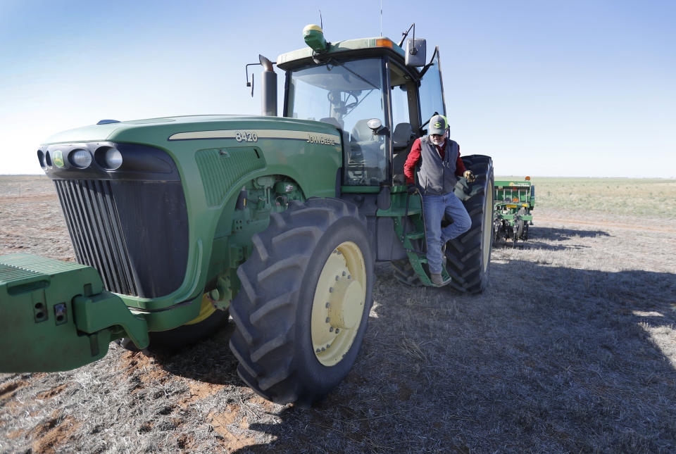 Tim Black climbs down from his tractor that he's using to sow grass on his Muleshoe, Texas, farm on Monday, April 19, 2021. The longtime corn farmer now raises cattle and plants some of his pasture in wheat and native grasses because the Ogallala Aquifer, needed to irrigate crops, is drying up. (AP Photo/Mark Rogers)