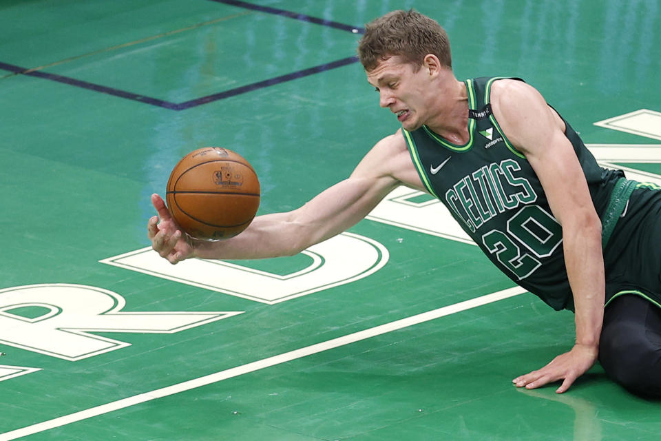 BOSTON, MASSACHUSETTS - MARCH 31: Moritz Wagner #20 of the Boston Celtics dives to keep the ball inbounds during the second half of the game against the Dallas Mavericks at TD Garden on March 31, 2021 in Boston, Massachusetts.