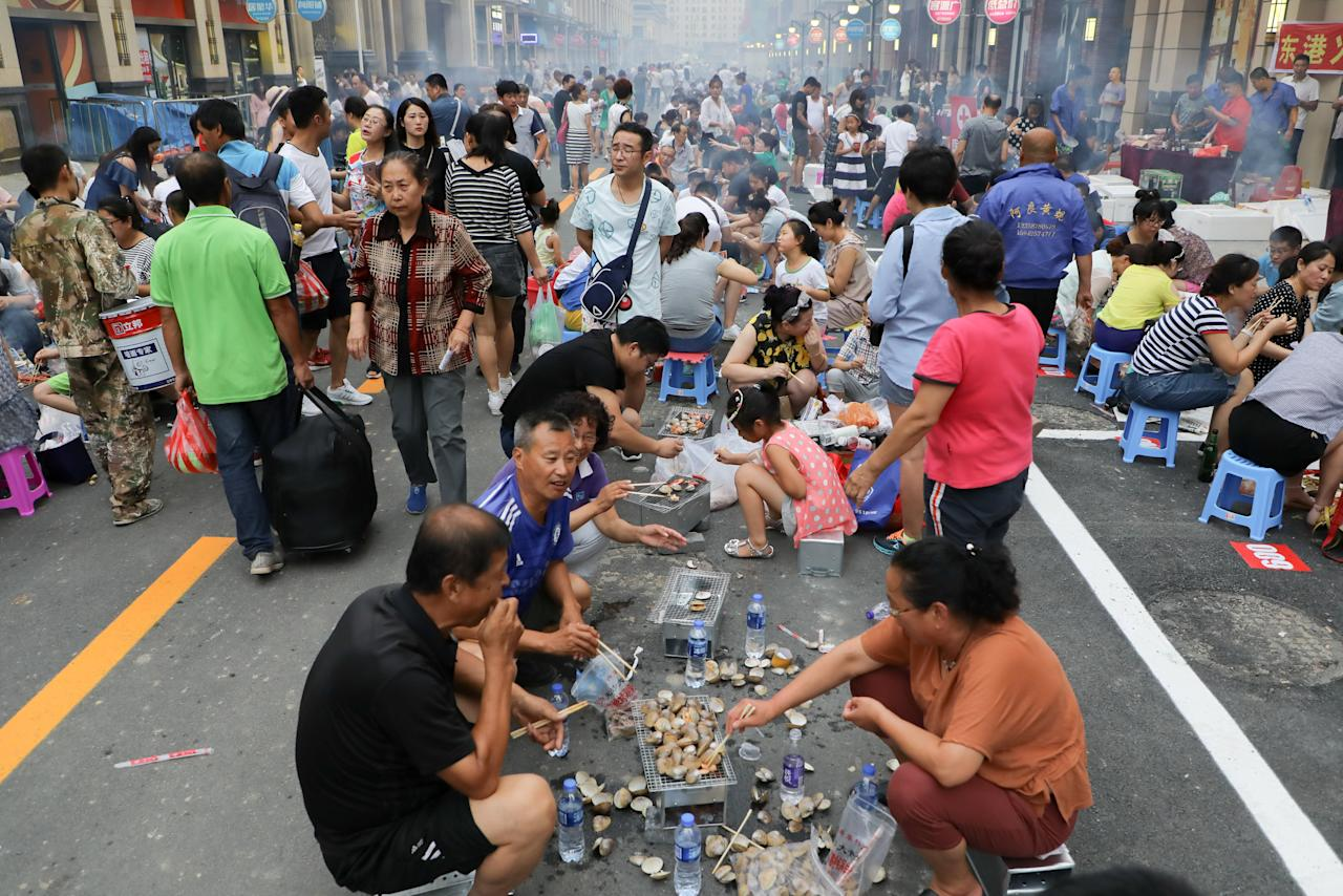 Thousands of people who participated in the event, cook and eat clams, famous local food, in Zhongjin Street in Dandong, Liaoning province, China, July 28, 2017. Picture taken July 28, 2017. REUTERS/Stringer ATTENTION EDITORS - THIS IMAGE WAS PROVIDED BY A THIRD PARTY. CHINA OUT. NO COMMERCIAL OR EDITORIAL SALES IN CHINA.