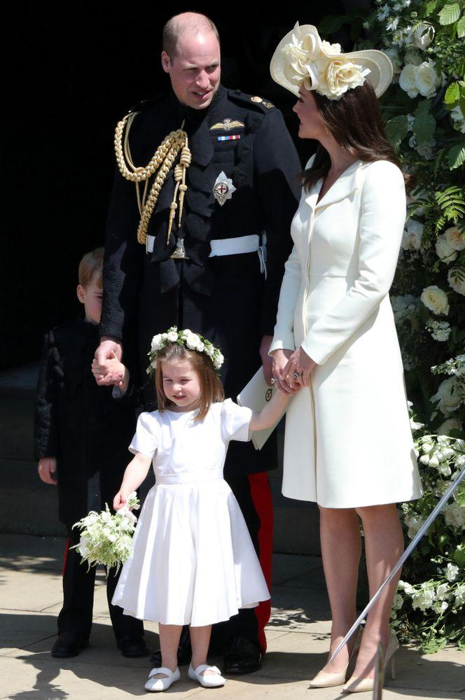 Princess Charlotte and Prince George (behind Prince Willam) with Princess Kate at the wedding of Meghan and Harry.