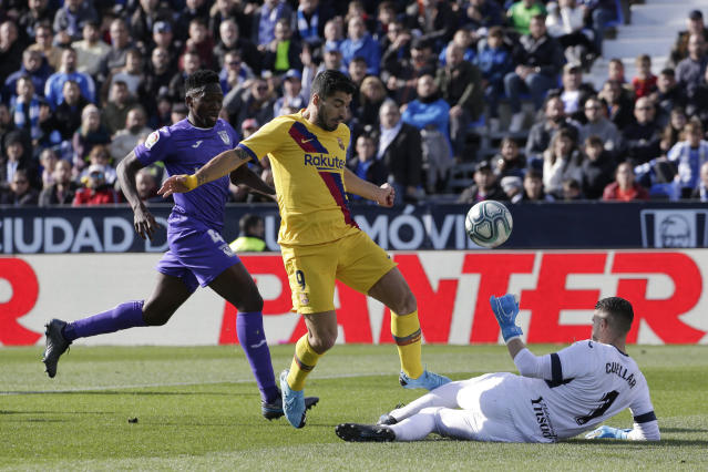 Leganes' goalkeeper Ivan Cuellar, right, makes a save in front Barcelona's Luis Suarez, center, during a Spanish La Liga soccer match between Leganes and FC Barcelona at the Butarque stadium in Madrid, Spain, Saturday Nov. 23, 2019. (AP Photo/Paul White)