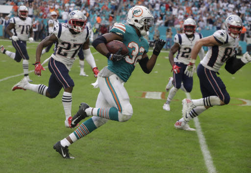 FILE - In this Dec. 9, 2018, file photo, Miami Dolphins running back Kenyan Drake (32) runs for a touchdown during the second half of an NFL football game against the New England Patriots, in Miami Gardens, Fla. The NFL revealed 70 of the 100 greatest plays in league history on Friday night with a TV special produced by NFL Films that has everything from spectacular offensive performances to defensive gems. In balloting conducted by The Associated Press, 68 media members on a nationwide panel voted for their top 100. Among those disclosed is the play some have dubbed The Drake Escape. (AP Photo/Lynne Sladky, File)