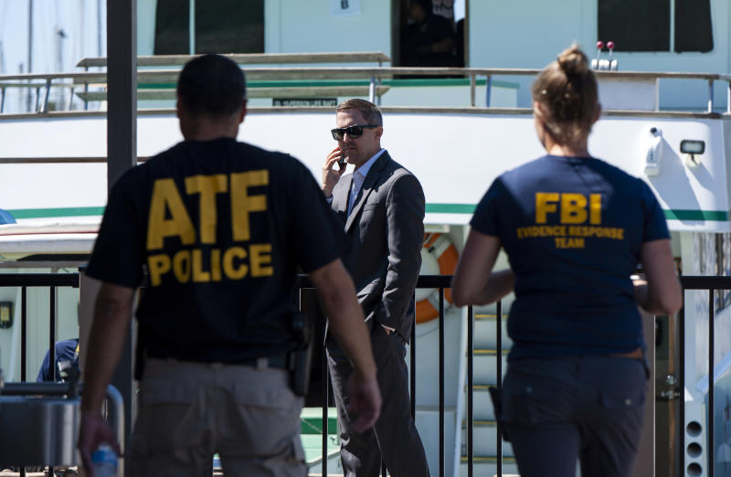 FILE - In this Sept. 8, 2019 file photo, investigators check the Truth Aquatics office on the Santa Barbara Harbor in Santa Barbara, Calif. Authorities conducting a criminal investigation into the deadly scuba diving boat fire off the coast of Southern California last week plan to interview previous patrons of the boat company to determine what kind of safety information they were provided during trips, a law enforcement source said. (AP Photo/Christian Monterrosa, File)