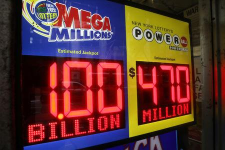 Signs display the jackpots for the Mega Millions and Powerball lottery drawings in New York City