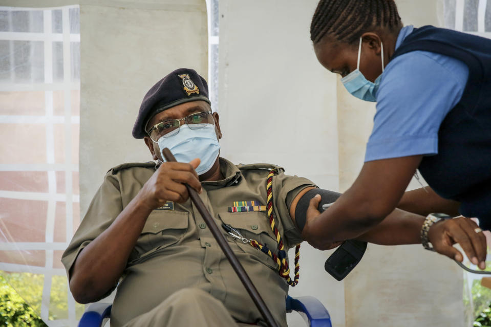 A police officer has his blood pressure taken before receiving a shot of the AstraZeneca COVID-19 vaccine, manufactured by the Serum Institute of India and provided through the global COVAX initiative, in Machakos, Kenya, Wednesday, March 24, 2021. AstraZeneca's repeated missteps in reporting vaccine data coupled with a blood clot scare could do lasting damage to the credibility of a shot that is the linchpin in the global strategy to stop the coronavirus pandemic, potentially even undermining vaccine confidence more broadly, experts say. (AP Photo/Brian Inganga)