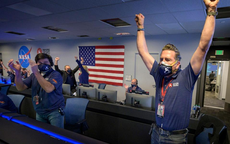 Members of Nasa's Perseverance rover team react in mission control  - Bill Ingalls/NASA