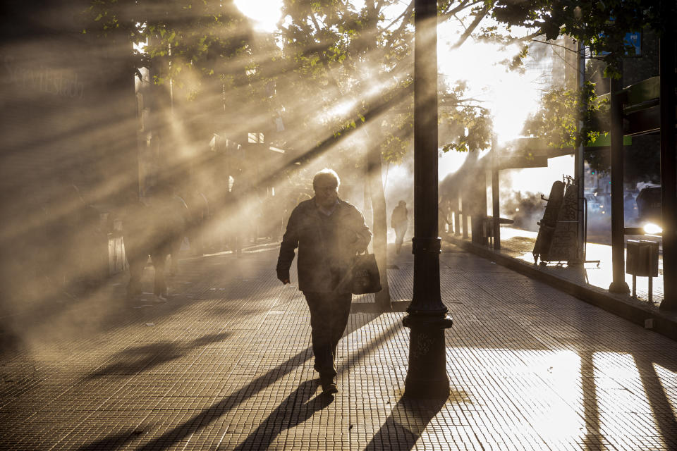 A pedestrian quickens his pace to escape the fumes caused by tear gas tear launched by police during a protest against the rising cost of subway and bus fares, in Santiago, Friday, Oct. 18, 2019. (Photo: Esteban Felix/AP)