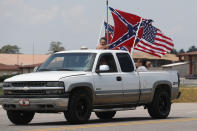 Race fans fly Confederate battle flags and a United States flag as they drive by Talladega Superspeedway prior to a NASCAR Cup Series auto race in Talladega Ala., Sunday, June 21, 2020. (AP Photo/John Bazemore)
