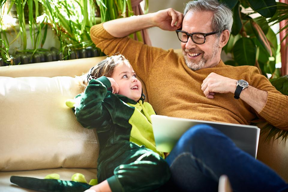 Modern grandfather sitting with granddaughter having fun and relaxing, childcare, connections, role model